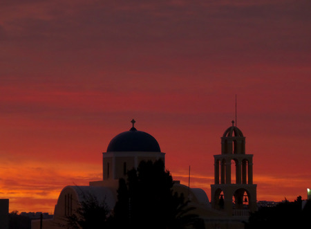 afterglow: Beautiful Orange and Purple Sunset Afterglow over Cyclades Style Church, Santorini Island of Greece