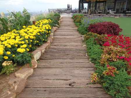 front yard: Colorful Flower Bed along the Wooden Walkway of the Front yard