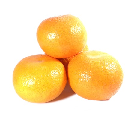 Close-up of piled up ripe vivid color oranges isolated on white background