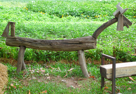botanical farms: Horse shaped dark brown wooden bench in a bright green botanical garden Stock Photo