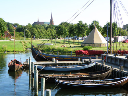 Moored Boats at the Pier and Roskilde Citys Famous Landmark St. Luke Cathedral, Roskilde, Denmark