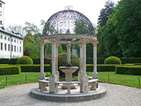 Gorgeous white pavilion with mini fountain of the English Garden, Innsbruck, Austria Stock Photo
