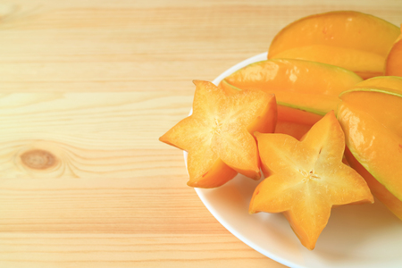 Vibrant color ripe Star Fruit, sliced and whole on wooden table, with free space for text and design Stock Photo