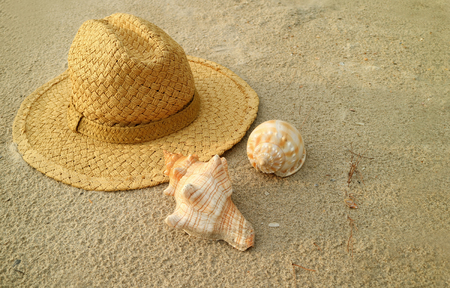 Natural brown straw hat with beautiful natural seashells on the sand beach of Thailand