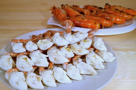 blue swimmer crab: Steamed Blue Crab Legs and Grilled Whole River Prawns Served on White Plates Stock Photo