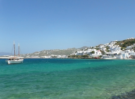 White fishing boat and little town between blue sky and blue sea, Mykonos Island, Greece