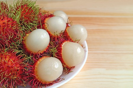 Plate of Ripe Rambutan Whole Fruits and Opened to Show Juicy White Meat on Wooden Table Stock Photo