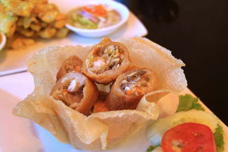 Deep fried spring rolls in a crispy eatable bowl served with fresh sliced vegetable