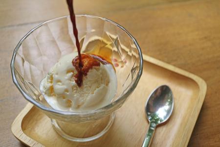 Start pouring espresso coffee onto vanilla ice cream for a tasty Affogato