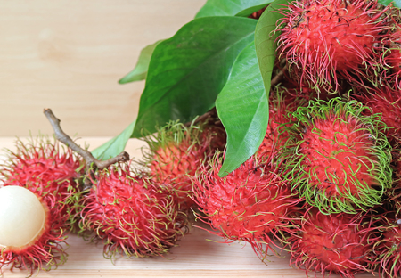 Bunch of Fresh Ripe Rambutan Whole Fruits and Opened to Show Delectable Juicy White Meat
