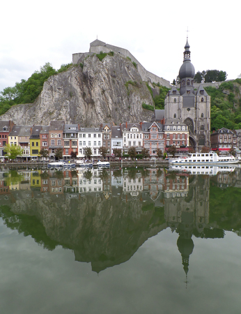 Reflections of gorgeous church and architecture on the Meuse river at Dinant, Wallonia region, Belgium