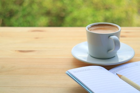 caffeine free: Hot Coffee with Lined Note Papers on the Wooden Table of Outdoor Seating, Blurred Green Bush in Background