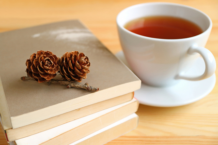 Rose pine cones on a stack of books with blurred background of a cup of hot tea Stock Photo