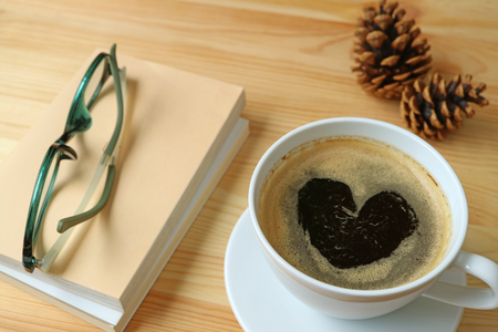 Cup of hot coffee with heart shape foam on wooden table with some books, glasses and pine cones