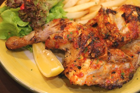 piri: Closed up flame grilled spicy chicken with a piece of lemon and green salad