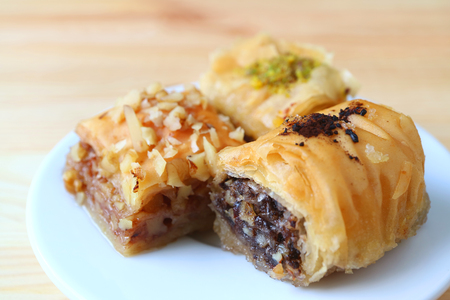 Closed up Three Types of Baklava Sweets on White Plate Served on Wooden Table, Blurred Background