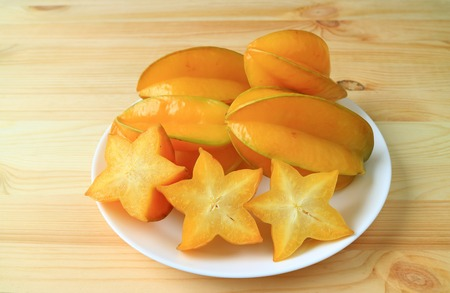 Many vibrant color ripe whole fruits and sliced Star Fruit on a white plate served on wooden table Stock Photo