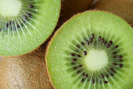 Closed up texture of cut in half vibrant green fresh and juicy ripe kiwi fruit