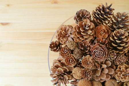 space for type: Top view of many different type and different size of natural dry pine cones in a glass bowl, with free space for text and design