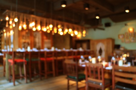 Blurred wooden interior of the restaurant in warm color with bokeh light, Background 写真素材