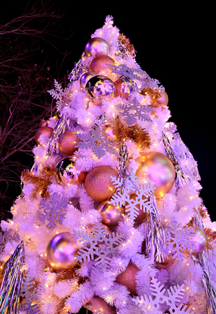pink colored light up big christmas tree full of glitter and shiny ornaments stock photo