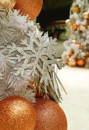 closed up silver glitter snowflake and pink gold ball shaped christmas ornaments with blurred christmas