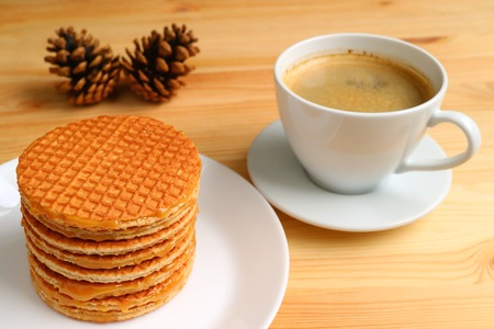 Stack of delectable Stroopwafel served on white plate and a cup of hot coffee on wooden table, with blurred pine cones in background