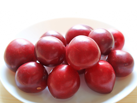 Closed up Red Color Ripe Gulf Ruby Plum Fruits Piled up on White Plate 스톡 콘텐츠