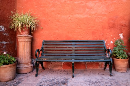 Black wooden bench in front of orange color rough wall with many terracotta planters, Santa Catalina Monastery in Arequipa of Peru Stock Photo