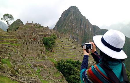 Young woman taking picture of the Inca ruins in Machu Picchu Banco de Imagens
