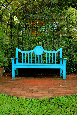Vertical photo of a vivid blue colored wooden bench on terracotta brick pathway in green garden