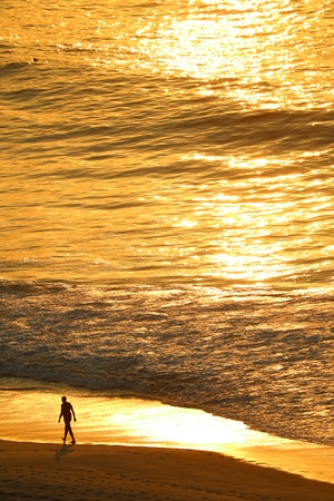 Aerial view of the Atlantic ocean in morning sunlight reflection with silhouette of a man walking on the Copacabana beach, Rio de Janeiro of Brazil