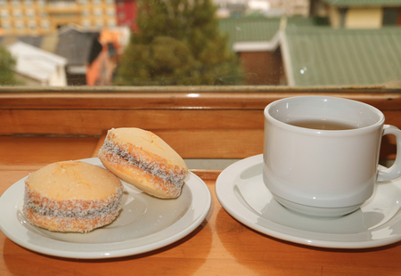 Pair of Alfajores, Traditional Latin American Sweets and a Cup of Hot Tea Served on Wooden Table by the Window, Ushuaia, Argentina 스톡 콘텐츠