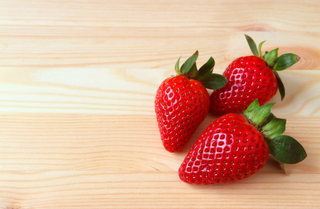 Three Vibrant Red Color Fresh Ripe Strawberry Fruits Isolated on Wooden Table with Free Space for Text or Design