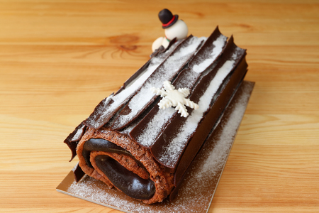 Delectable Buche de Noel or Chocolate Yule Log Cake for Christmas Sprinkle with Icing Sugar on the Wooden Table Archivio Fotografico