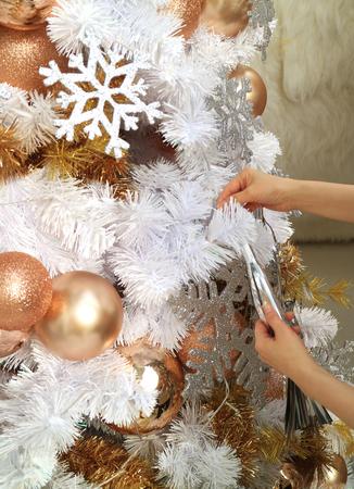 Manos de mujer sosteniendo un adorno para decorar el hermoso árbol de Navidad blanco y dorado