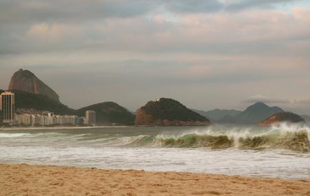 Copacabana beach striking by ocean waves, with Sugarloaf Mountain in backdrop, Rio de Janeiro of Brazil