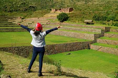 Female tourist raising her arms feeling impressed with Inca stepped agricultural ruins of Tipon archaeological site in the Sacred Valley, Cusco, Peru 免版税图像