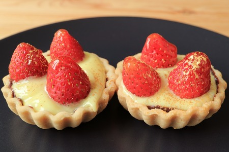 Closed up a pair of yummy mini custard cream tarts topped with fresh strawberries and edible gold powder served on black plate
