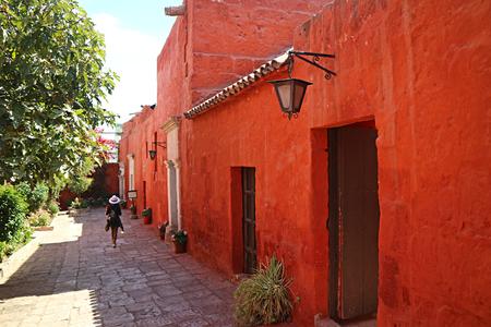 Female tourist walking along deep orange colored historic buildings in Santa Catalina Monastery, Arequipa, Peru Stockfoto