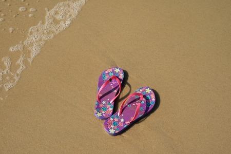 A pair of vibrant purple flip-flops sandals on the sandy beach with the wave swash, Copacabana beach, Brazil