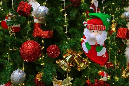 Świąteczna skarpeta Mikołaja z wieloma jaskrawymi kolorowymi ozdobami wiszącymi na błyszczącej choince