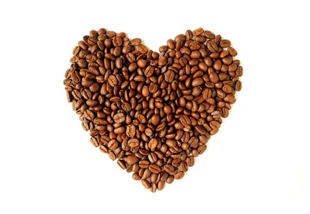 Top view of heap of roasted coffee beans in heart shaped isolated on white background