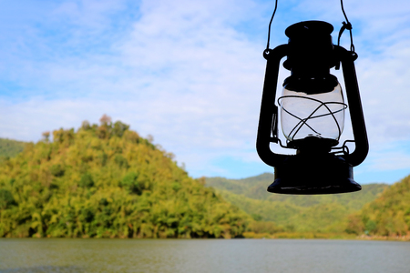 Closed up silhouette of retro oil lantern against the morning sky of Hoob Khao Wong Reservoir, Suphanburi province, Thailand