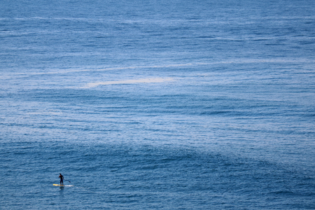 Man rowing stand-up paddleboard over the Atlantic ocean, Copacabana beach, Rio de Janeiro, Brazil