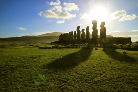 Silhouette of Moai statues against dazzling sunrise sky at Ahu Tongariki, the largest celemonial platform on Easter Island, Chile, South America