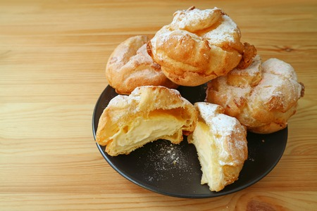 Choux a la Creme Pastries or French Cream Puffs Filled with Custard Cream Served on a Black Plate