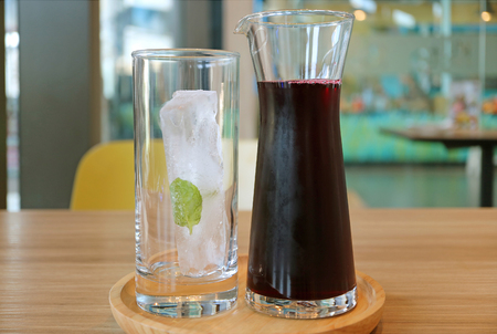 A Carafe of Roselle Juice with a Glass of Ice Cube on Wooden Tray Served on Wooden Table