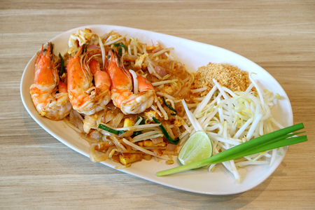 Pad Thai or Thai Style Fried Noodle Topped with River Prawns Served on Wooden Table