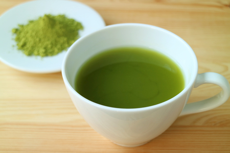 Closed Up a Cup of Hot Matcha Green Tea Served on Wooden Table with Blurry Plate of Matcha Tea Powder in Background 免版税图像
